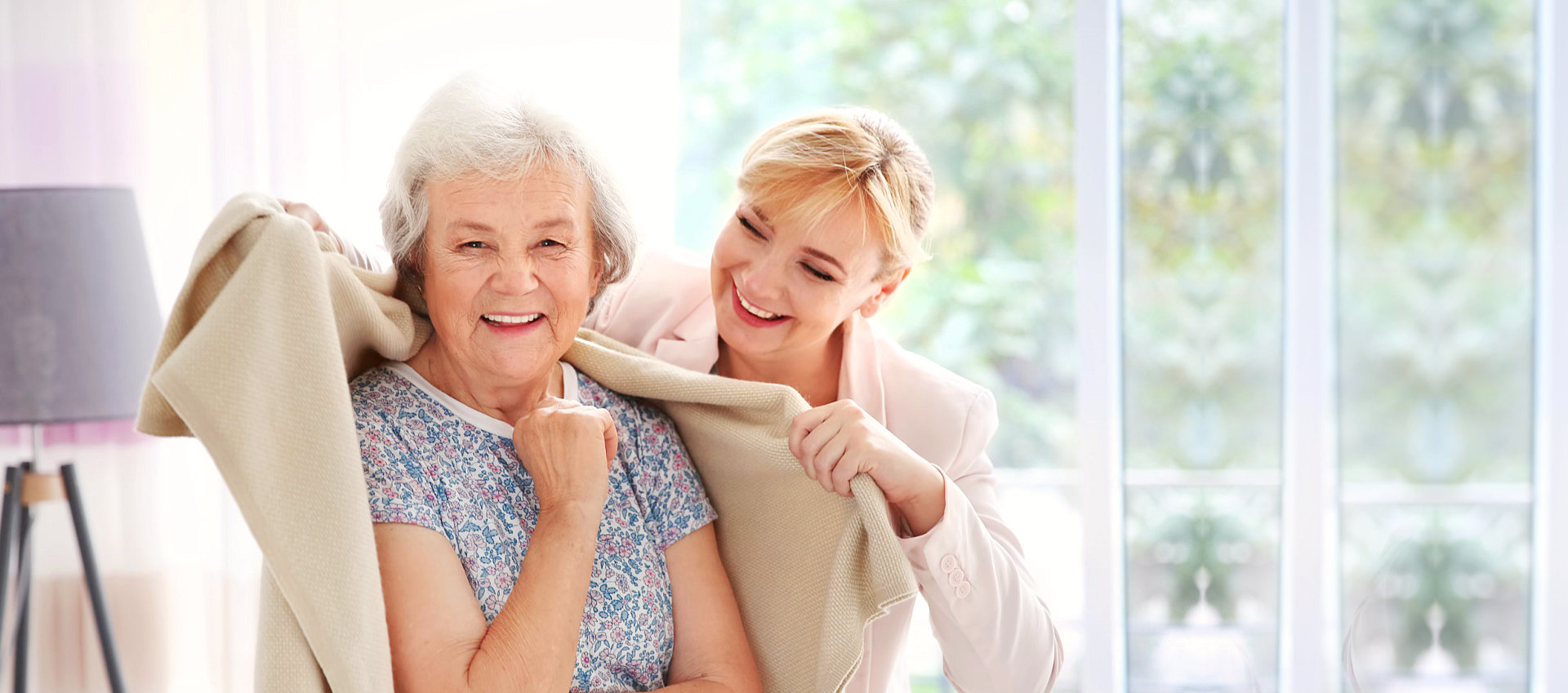 caregiver covering elderly woman with blanket