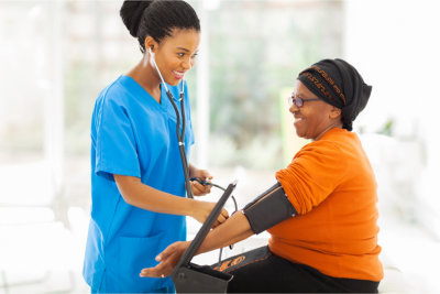nurse monitoring elderly woman's blood pressure
