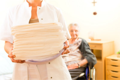 caregiver holding a pile of diaper