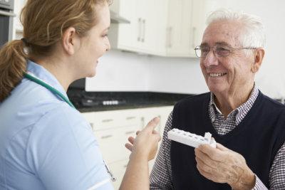 caregiver handling elderly man his medicine