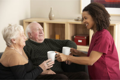 caregiver serving elderly couple a cup of hot drink