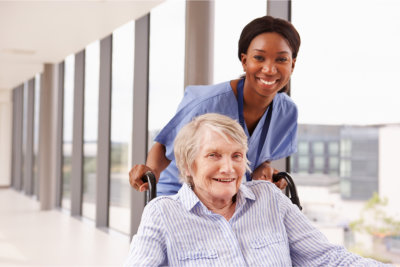 caregiver assisting elderly woman in a wheelchair