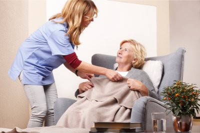 caregiver making elderly woman comfortable with the blanket